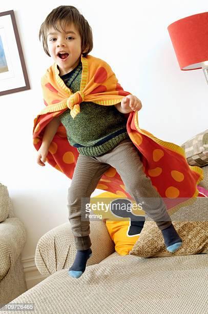 Little Boy Wearing Towel as Cape and Jumping on Couch