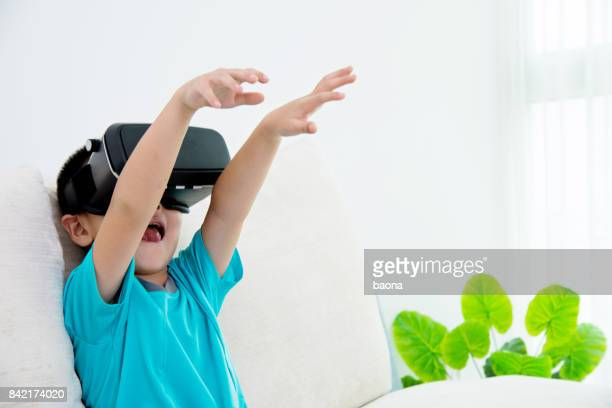 Little boy wearing virtual reality headset at home