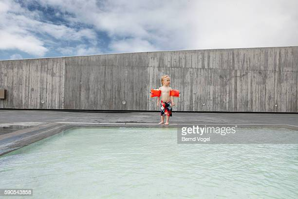 little boy (3-4) wearing water wings jumping in pool - arm band stock pictures, royalty-free photos & images