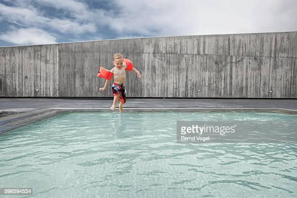 Little boy (3-4) wearing water wings jumping in pool