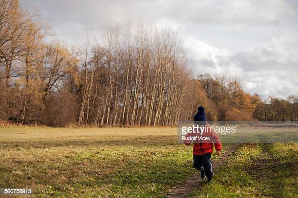 little boy wearing winter clothes running outdoors - februar stock-fotos und bilder