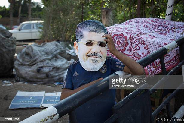 CONTENT] A little boy wears a mask of the deposed Egyptian president Mohammed Morsi at the Muslim Brotherhood sitin at the Rabaa Al Adaweyya mosque...