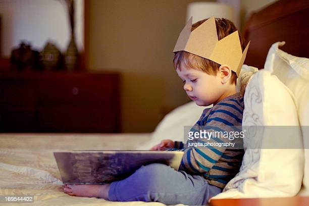 Little boy with a crown reading a book