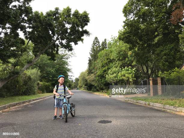 Little boy with a helmet on ready to ride to school