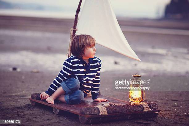 Little boy with a lantern on a raft