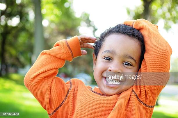 Menino com um sorriso de valor inestimável do lado de fora