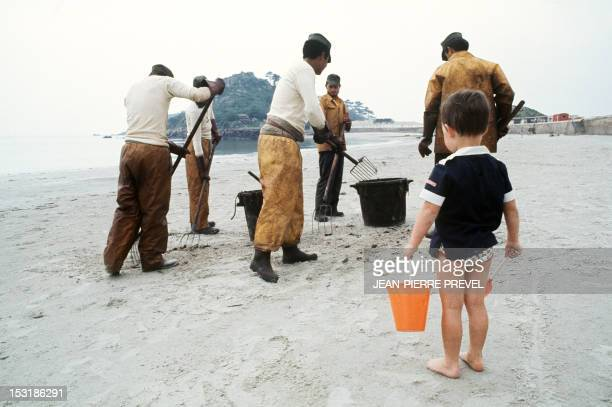 A little boy with a shovel and a bucket looks at people cleaning up a beach in Portsall in June 1978 after the Amoco Cadiz oil spill The Liberian oil...