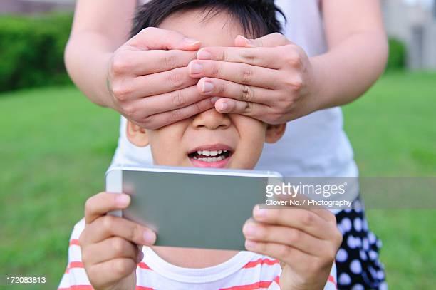 little boy with a smart phone. - augen zuhalten stock-fotos und bilder