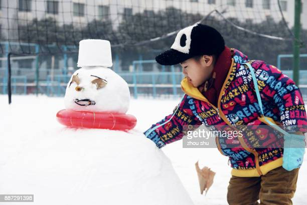 A little boy with a snowman