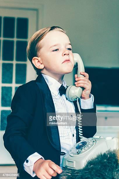Kleiner Junge mit einer Einstellung spricht auf alten Telefon