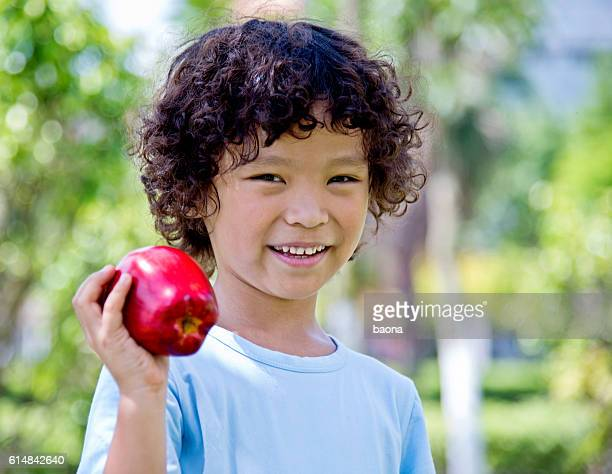 Little boy with apple outdoors
