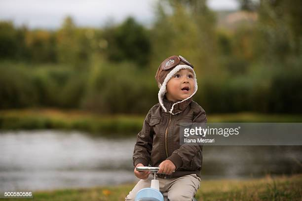 A little boy with aviator's hat and jacket outdoors