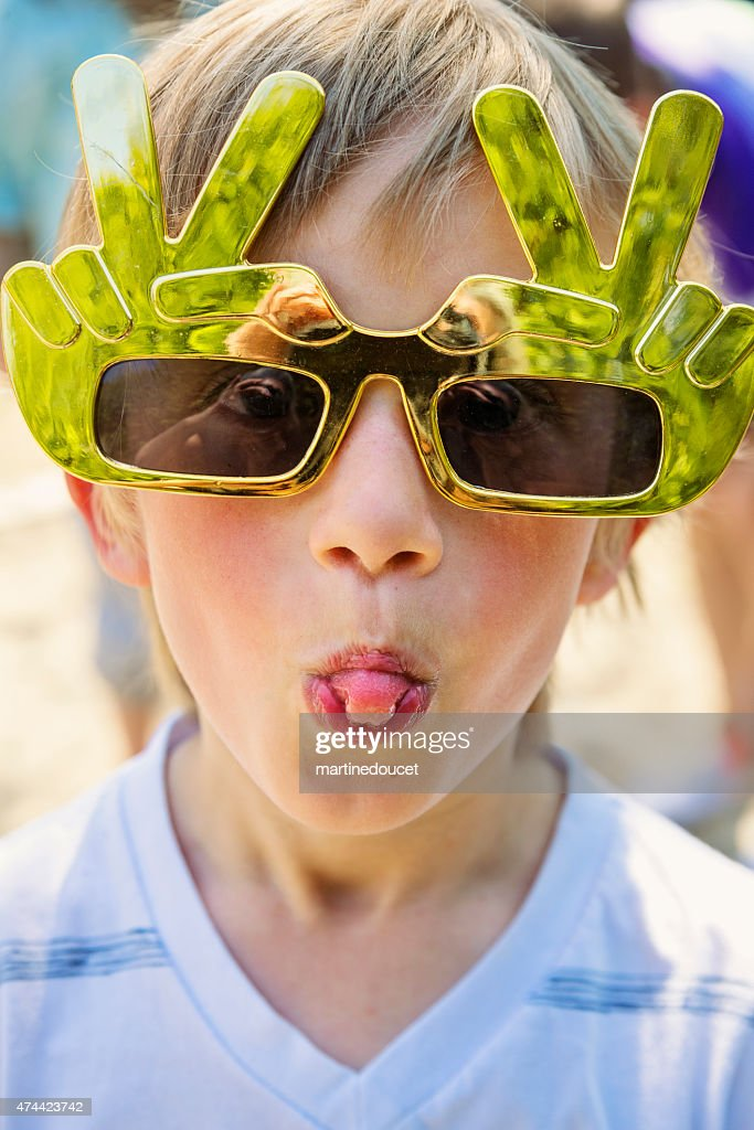 Little boy with big toy funny glasses sticking out tongue. : Stock Photo