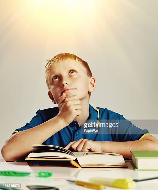 Little boy with book looks up toward inspiring light