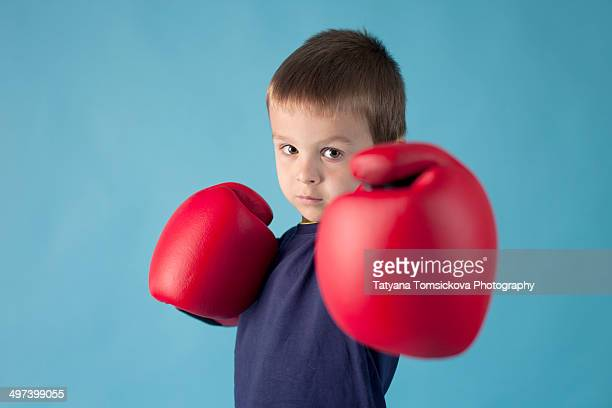 Little boy with boxing gloves on blue background