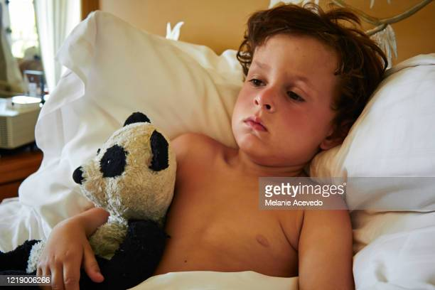 Little boy with brown curly hair laying in bed holding a stuffed panda toy.