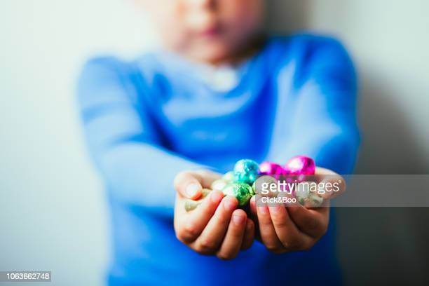 little boy with chocolate easter eggs in his hands - easter candy stock pictures, royalty-free photos & images