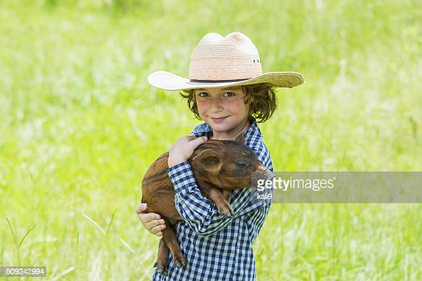 Little boy with cowboy hat holding baby pig