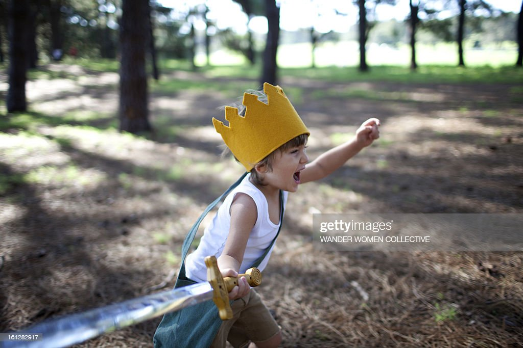 Little boy with crown running in forest with sword : Stock Photo