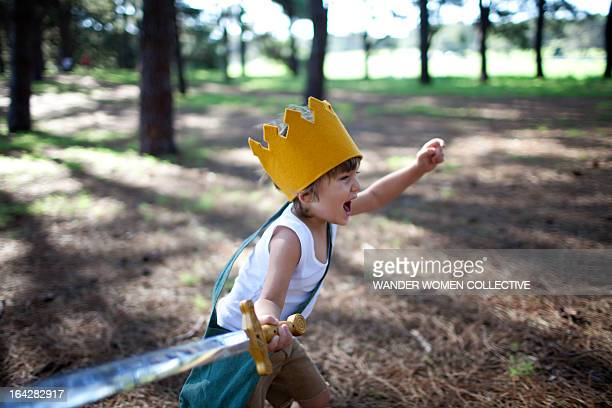 little boy with crown running in forest with sword - batalha guerra - fotografias e filmes do acervo