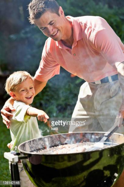 Little boy with dad grilling hamburgers