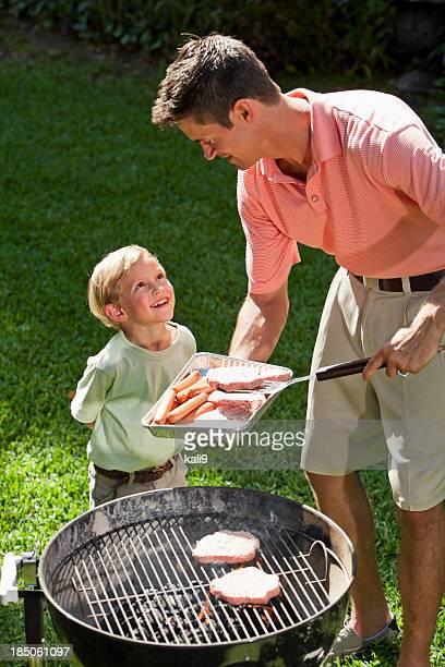 Kleiner Junge mit Vater Grillen hotdogs und Burger