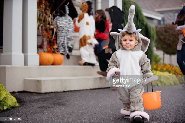 little boy with down syndrome and his friends dressed in halloween costumes - happy halloween stock photos and pictures