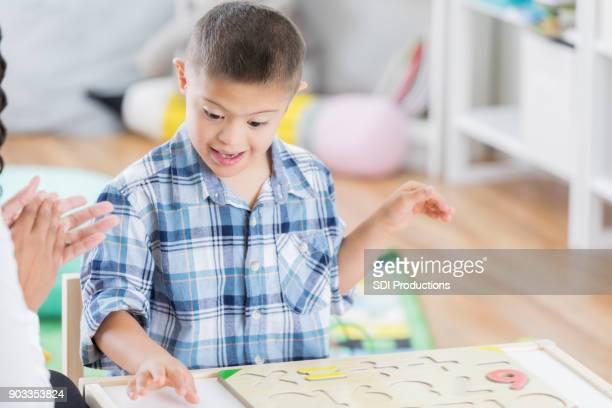 Little boy with Down syndrome enjoys praise from teacher
