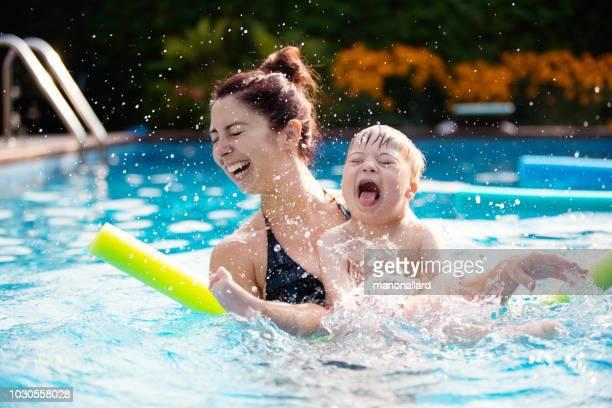 彼の家族と一緒にプールで楽しむことダウン症の少年