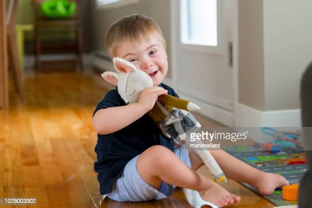 little boy with down syndrome plays with a little teddy bear. - dolly fox stock pictures, royalty-free photos & images