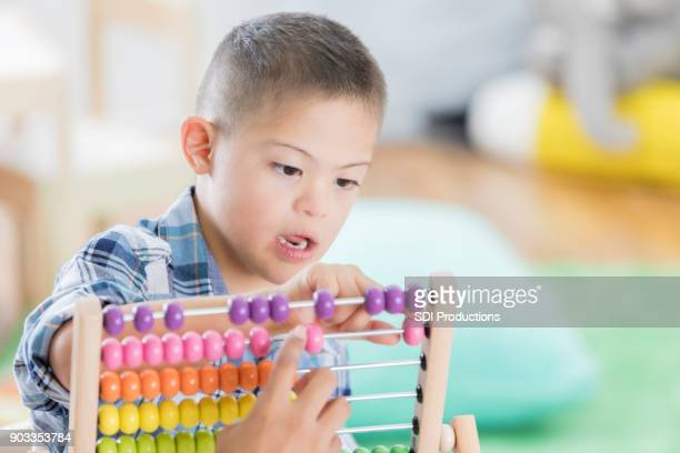 Little boy with Down syndrome uses abacus at school