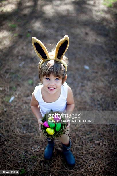 LIttle boy with Easter bunny ears and eggs in nest