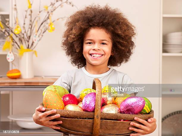 little boy with easter eggs in basket - african american easter stock photos and pictures