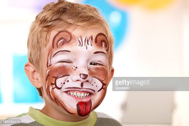 Little boy with face painted as lion on birthday party