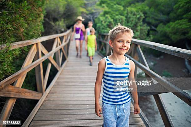 Little boy with family walking on a ramp through forest