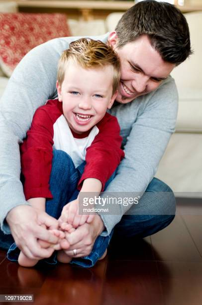 little boy with father - tickling feet stock photos and pictures
