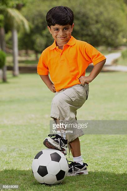 little boy with foot on soccer ball
