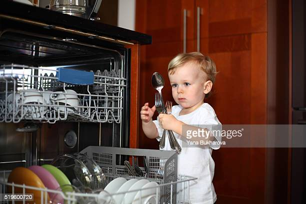 Little boy with forks and spoons near the dishwasher