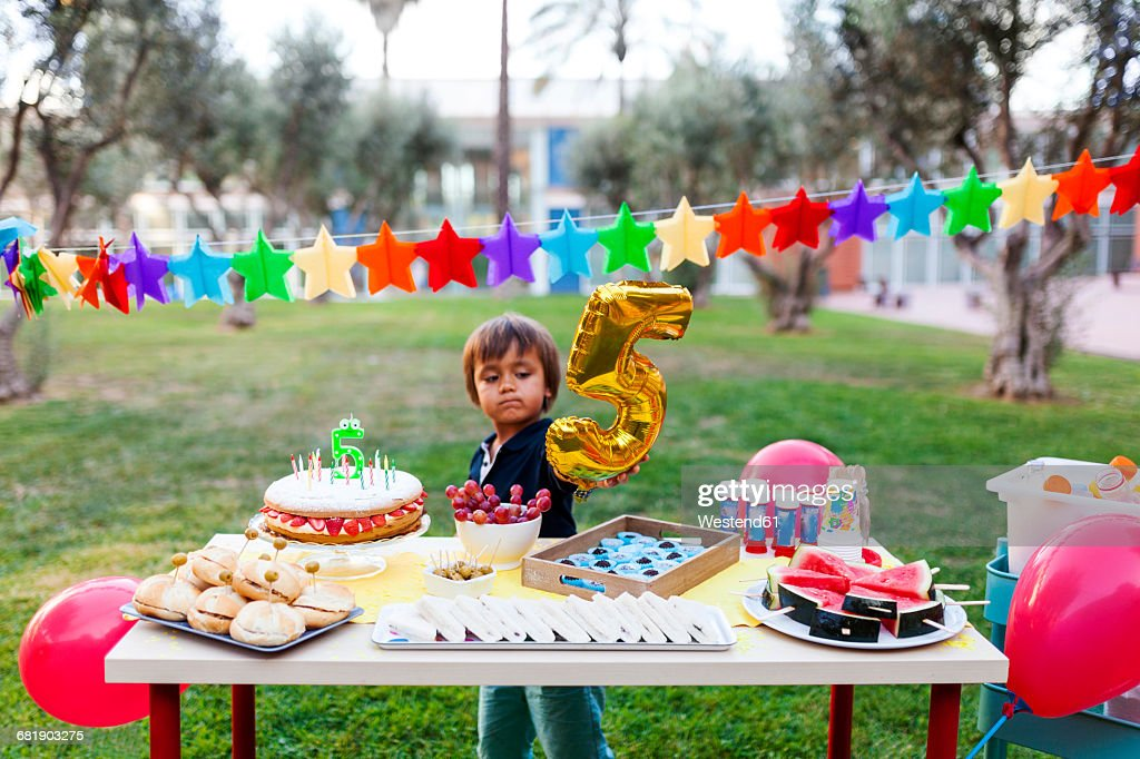 Little boy with golden balloon behind laid birthday table : Stock Photo
