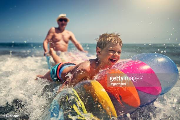 little boy with grandfather playing in sea waves - candid beach stock photos and pictures
