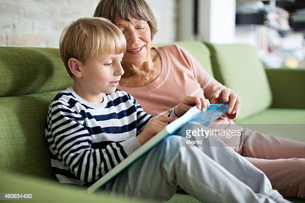 Kleiner Junge mit Großmutter, ein Buch zu lesen