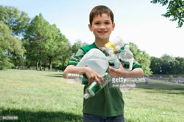 Little boy with handful of recycling