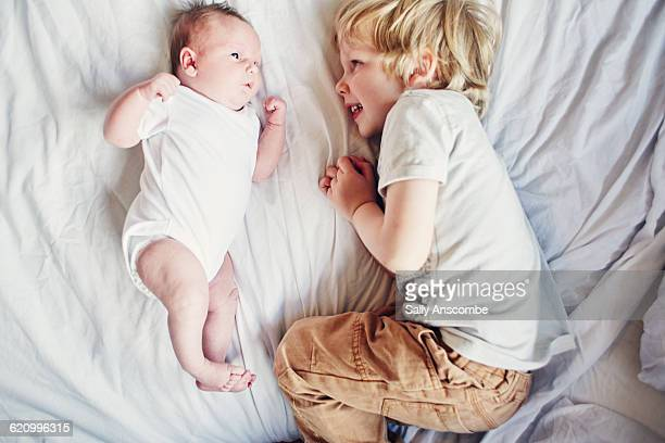little boy with his baby sister - sibling stock pictures, royalty-free photos & images