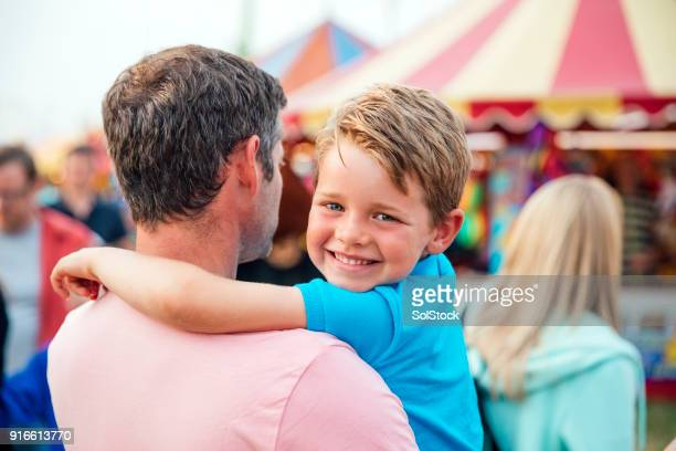 little boy with his dad at an amusement park - traveling carnival stock pictures, royalty-free photos & images