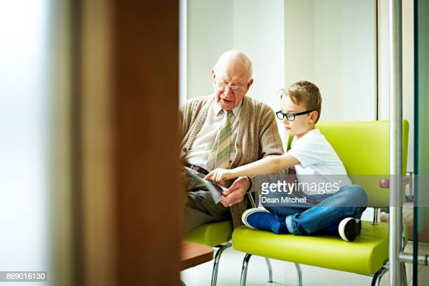 Little boy with his grandfather sitting in waiting room