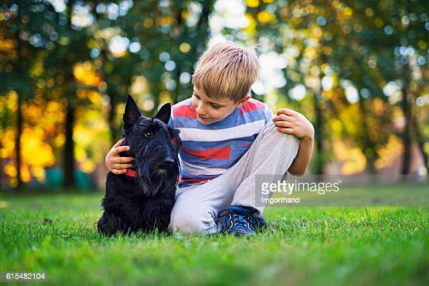 Little boy with his pet pal in autumn park