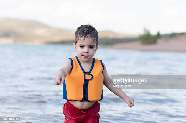 Little Boy with lifeboat on beach in a summer day, Spain