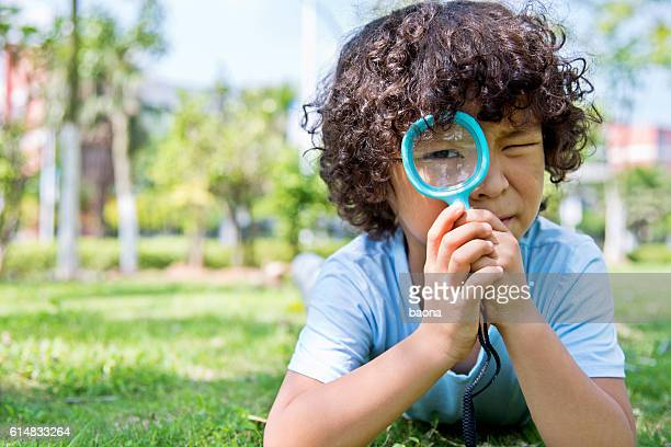Little boy with magnifying glass in park