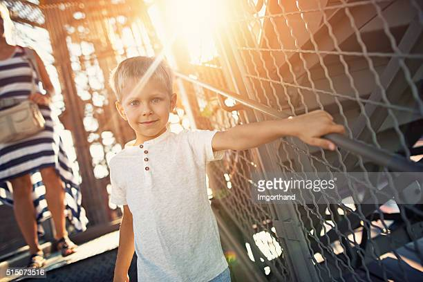 Little boy with mother climbing down stairs of Eiffel Tower