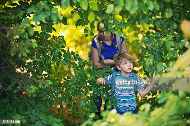 Little boy with mother hiking through a thick forest